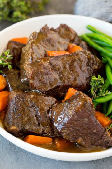 A bowl of Instant Pot short ribs in sauce with carrots and green beans.