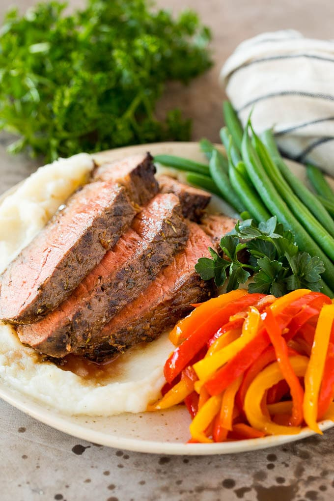 A plate of grilled beef, peppers and green beans.