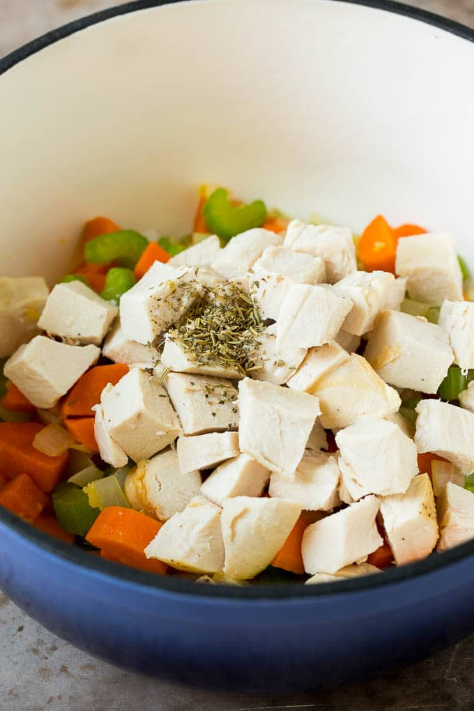 Diced chicken and herbs in a pot with vegetables.