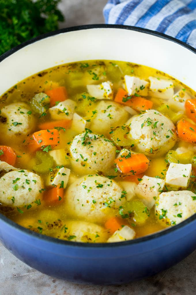 A pot of matzo ball soup with chicken and vegetables.