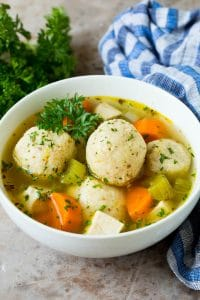 A bowl of matzo ball soup with chicken, garnished with parsley.