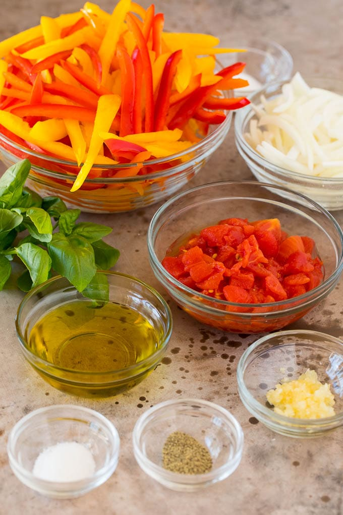 Ingredient bowls of tomatoes, olive oil, seasonings and peppers.