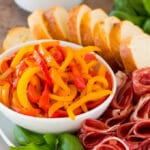 A bowl of peperonata served with cured meats, olives and bread.