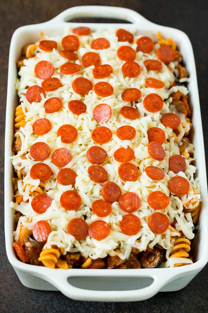 Pasta in a casserole dish topped with cheese and pepperoni.