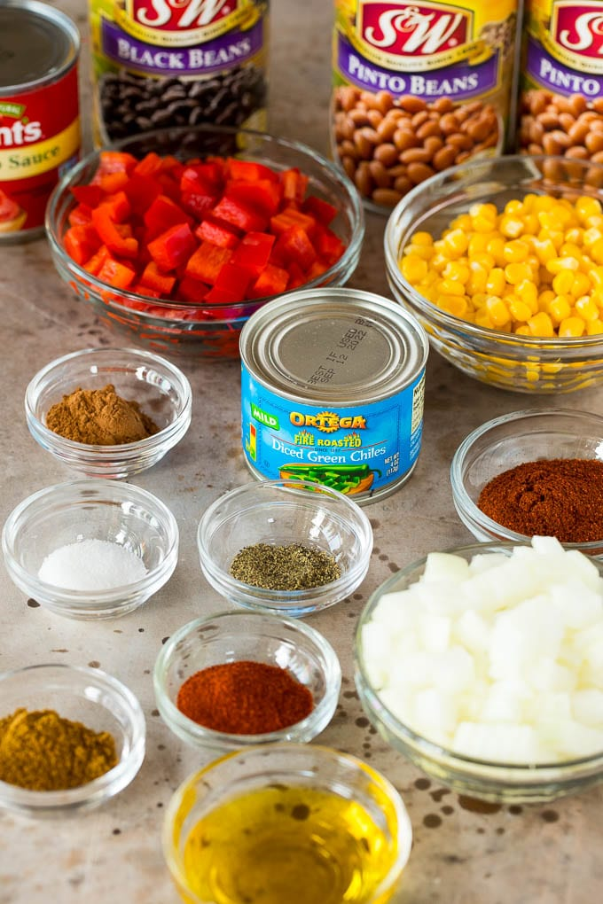 Chili ingredients in glass bowls including spices and vegetables.