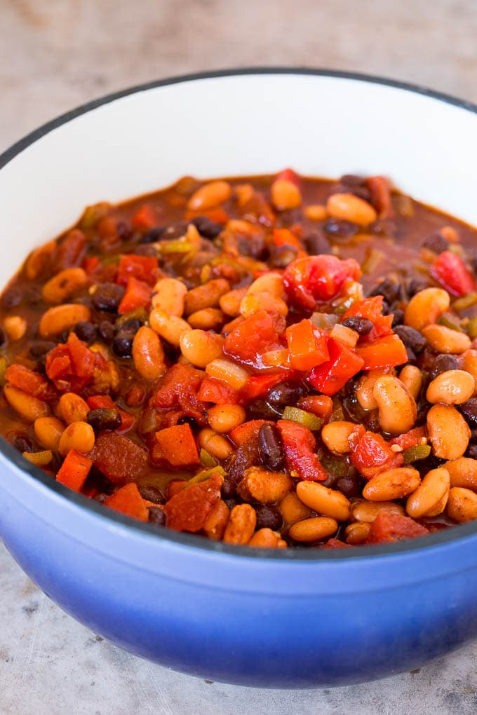 Beans, peppers, onions and tomatoes in a soup pot.