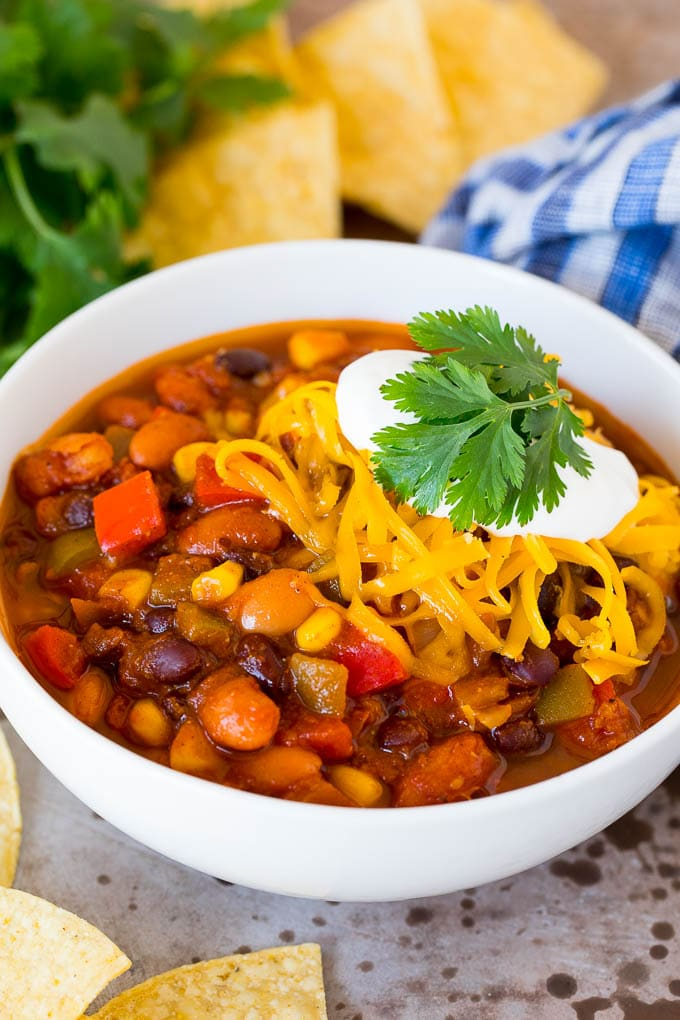 A bowl of vegetarian chili topped with shredded cheese and sour cream.
