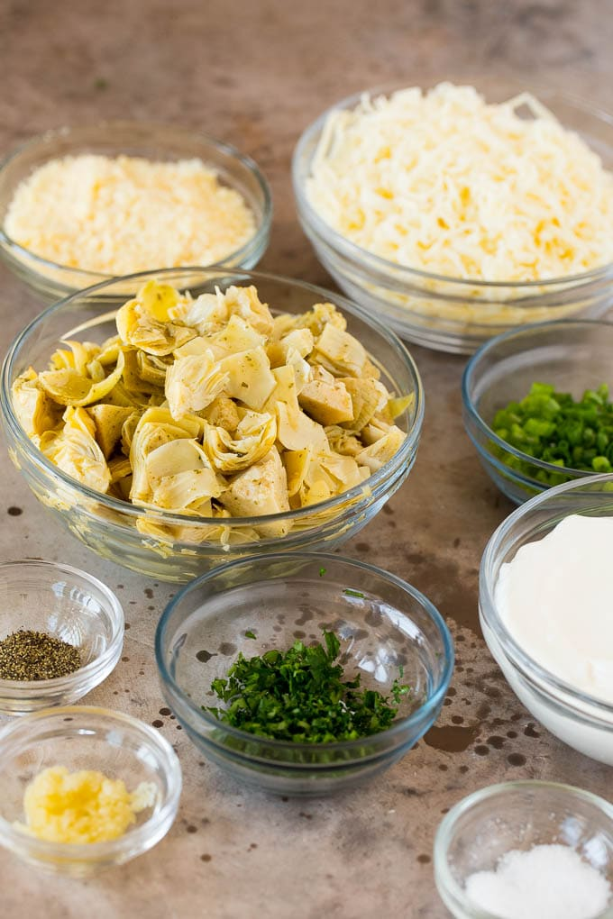 Glass bowls filled with sour cream, cheeses, artichokes and herbs.