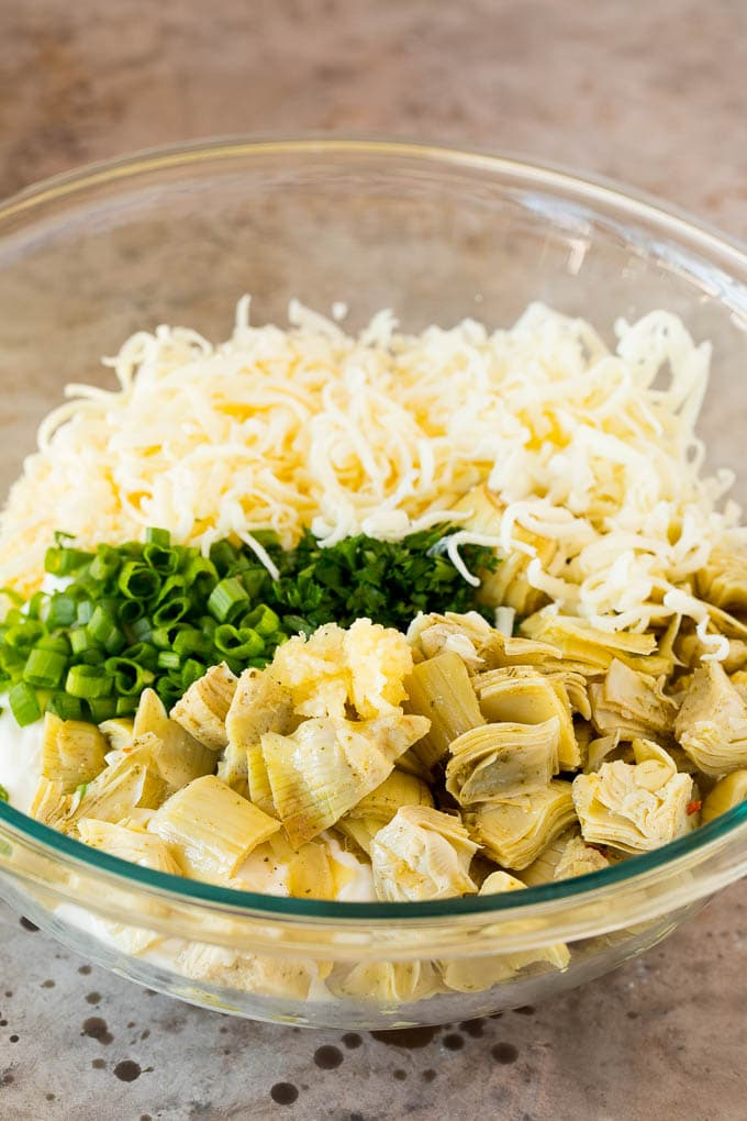 A bowl of three types of cheese, artichoke hearts and herbs.