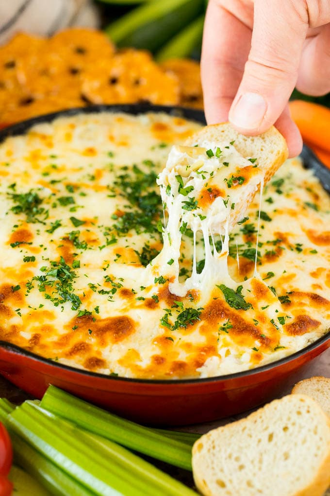 A skillet of artichoke dip with a hand reaching to take a serving.