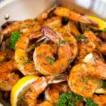 A pan of Cajun shrimp garnished with parsley and lemon.