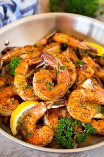 A pan of Cajun shrimp garnished with parsley and lemon.