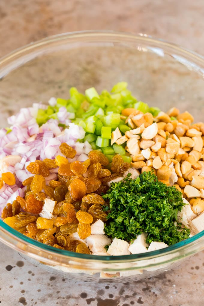 A bowl of diced chicken with raisins, cashews and vegetables.
