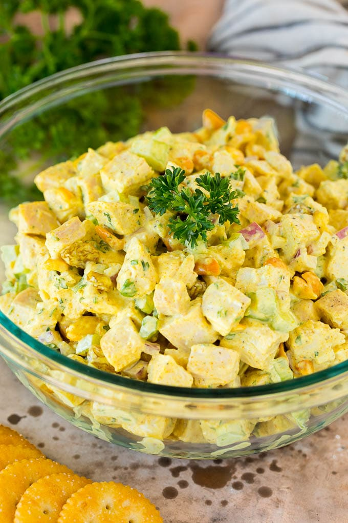 A serving bowl of curry chicken salad garnished with parsley.