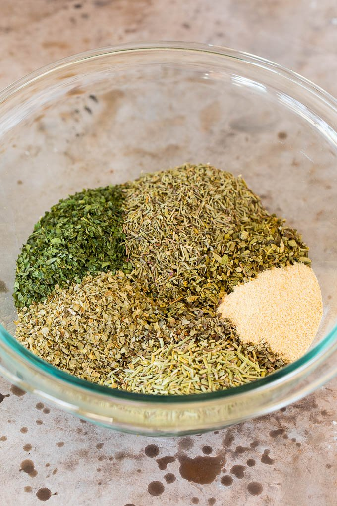 A mixing bowl with dried herbs and garlic powder in it.