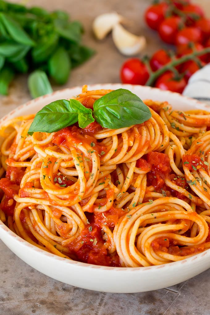 Italian seasoning sprinkled over a bowl of spaghetti.