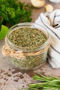 A jar of homemade Italian seasoning surrounded by fresh herbs.