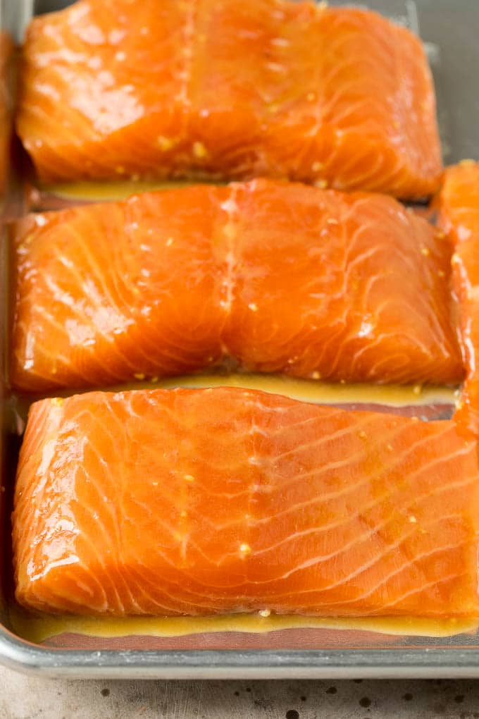 Marinated salmon pieces on a sheet pan.