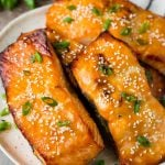 A platter of miso salmon fillets topped with sesame seeds and green onions.