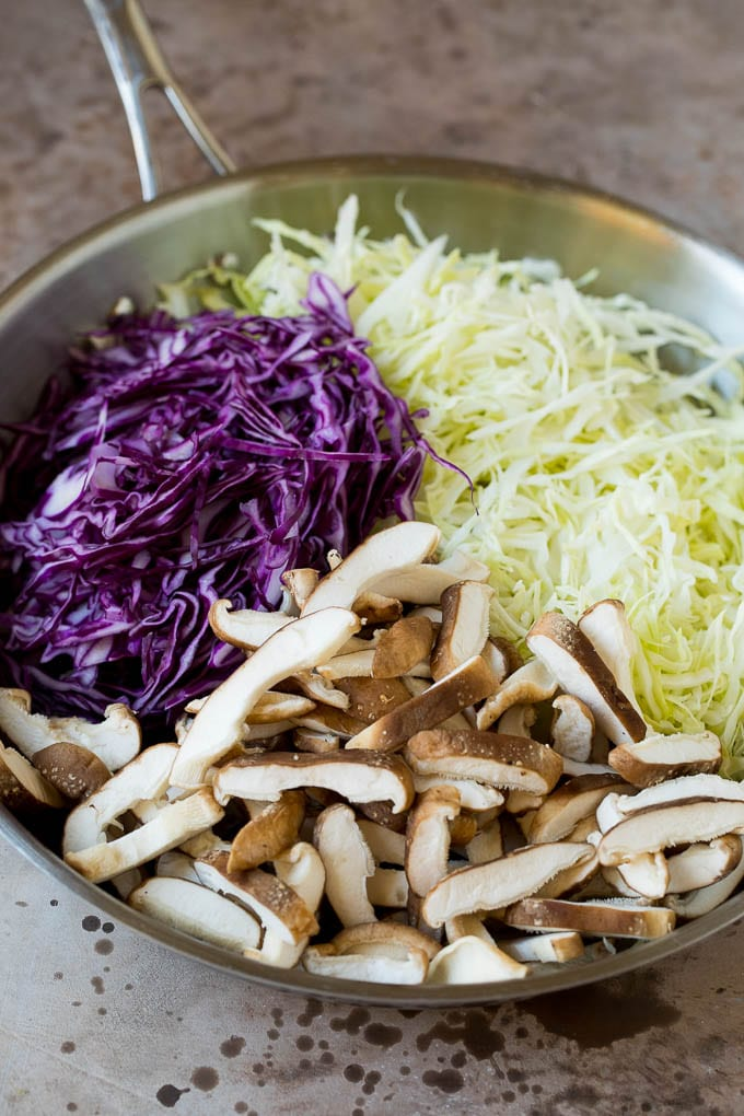 Shredded cabbage and sliced mushrooms in a skillet.