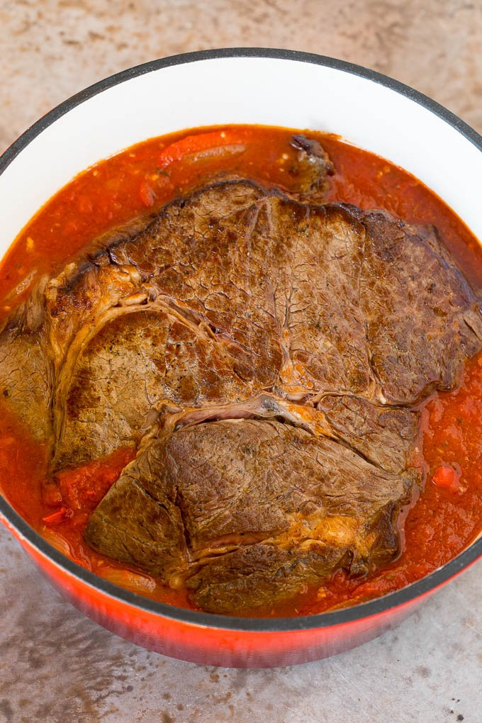 A seared roast in a pot of tomato and pepper sauce.