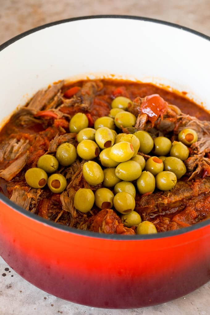 A pot of shredded beef with whole green olives on top.