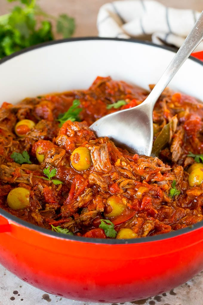 A serving spoon in a pot of ropa vieja with a garnish of cilantro.