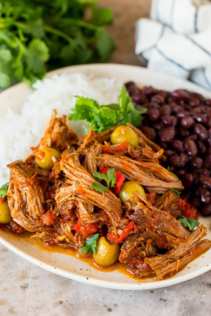 A plate of ropa vieja served with rice and black beans.