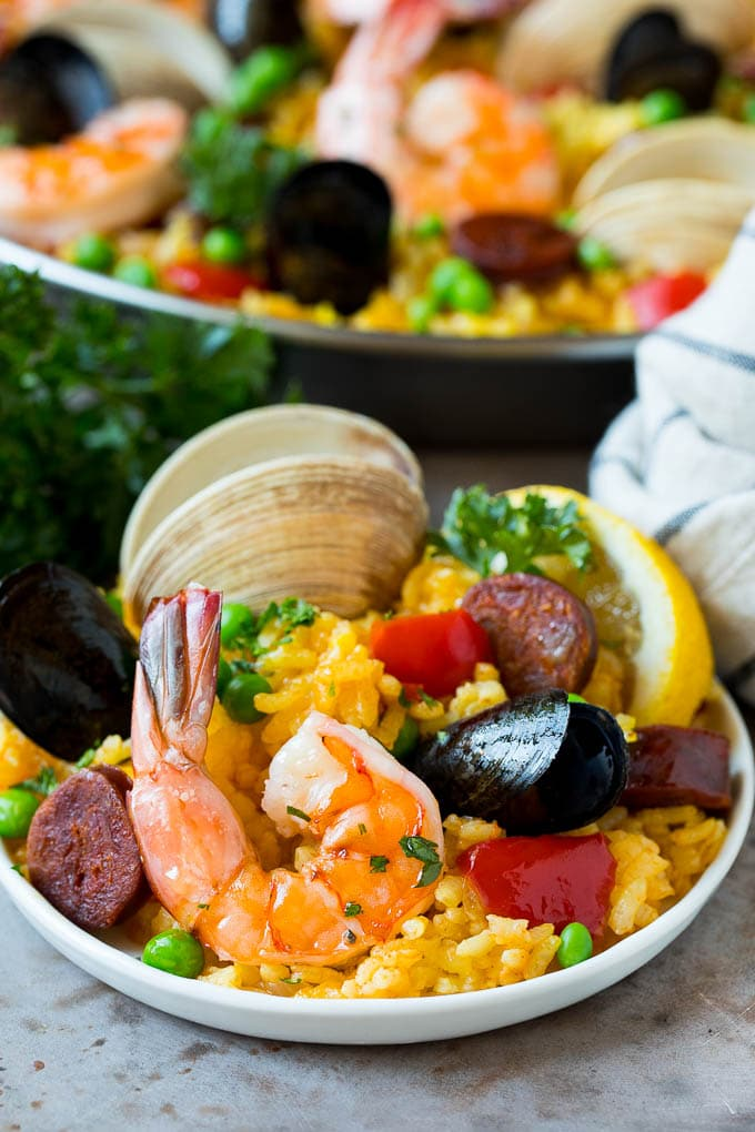 A plate of seafood paella garnished with parsley.