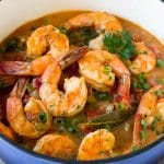 A pot of shrimp etouffee garnished with green onions and parsley.