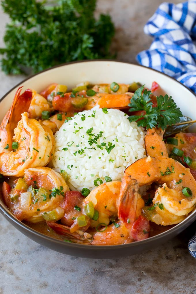 A bowl of shrimp etouffee served with rice.