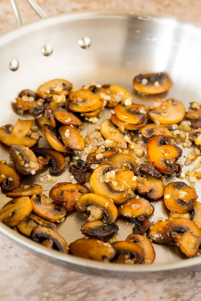 Sauteed mushrooms and shallots in a skillet.