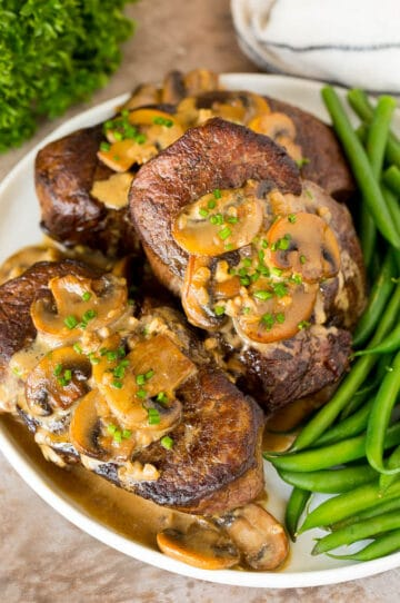 A plate of Steak Diane topped with mushroom sauce and served with green beans.