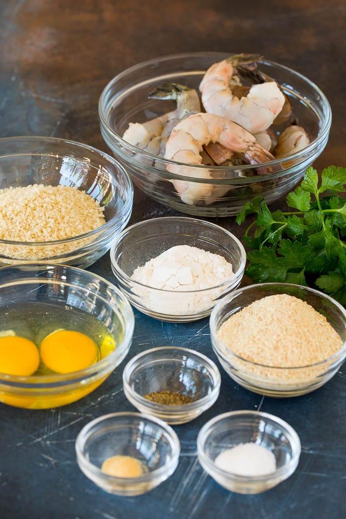 Bowls of breadcrumbs, seasonings and shrimp.