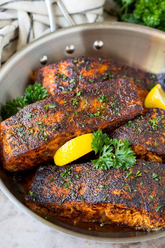 A pan of blackened salmon fillets garnished with lemon and parsley.