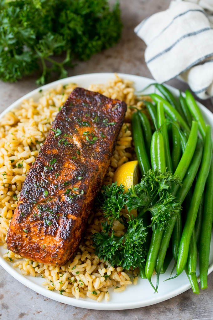 Blackened salmon served with rice and green beans.