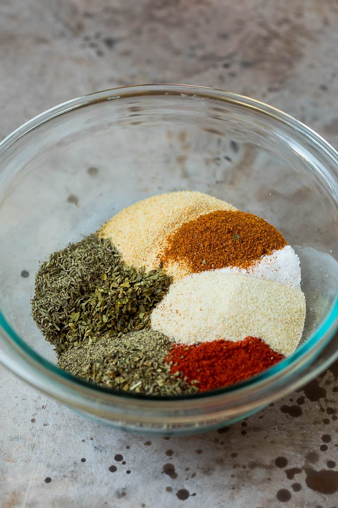 A mixing bowl filled with an assortment of spices and dried herbs.