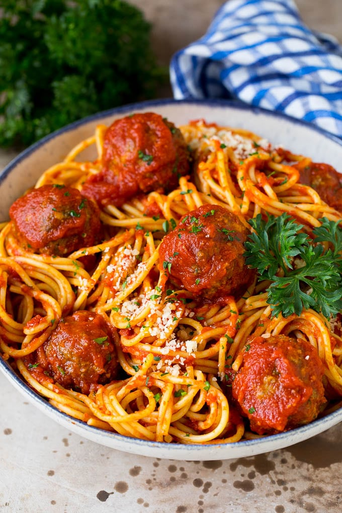 A serving bowl of crock pot spaghetti topped with meatballs and grated cheese.