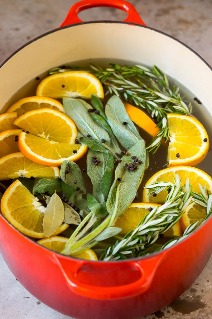A pot of brine with oranges, herbs and peppercorns.