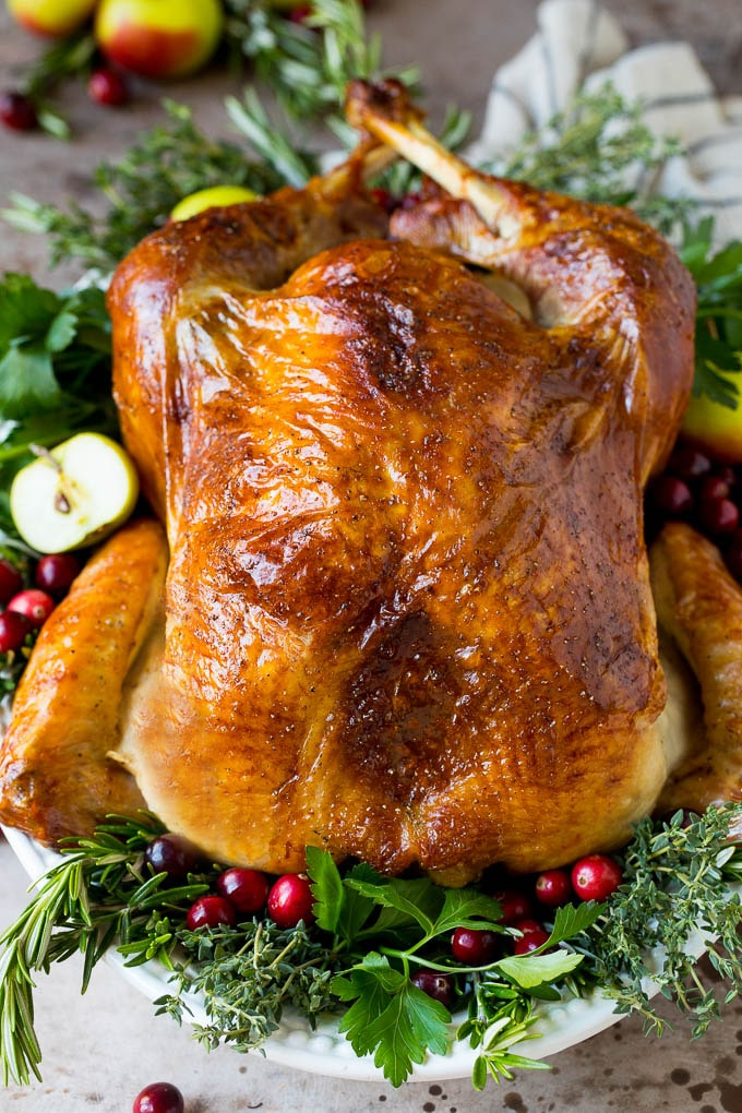 Learn how to brine a turkey to make this cooked turkey garnished with herbs.