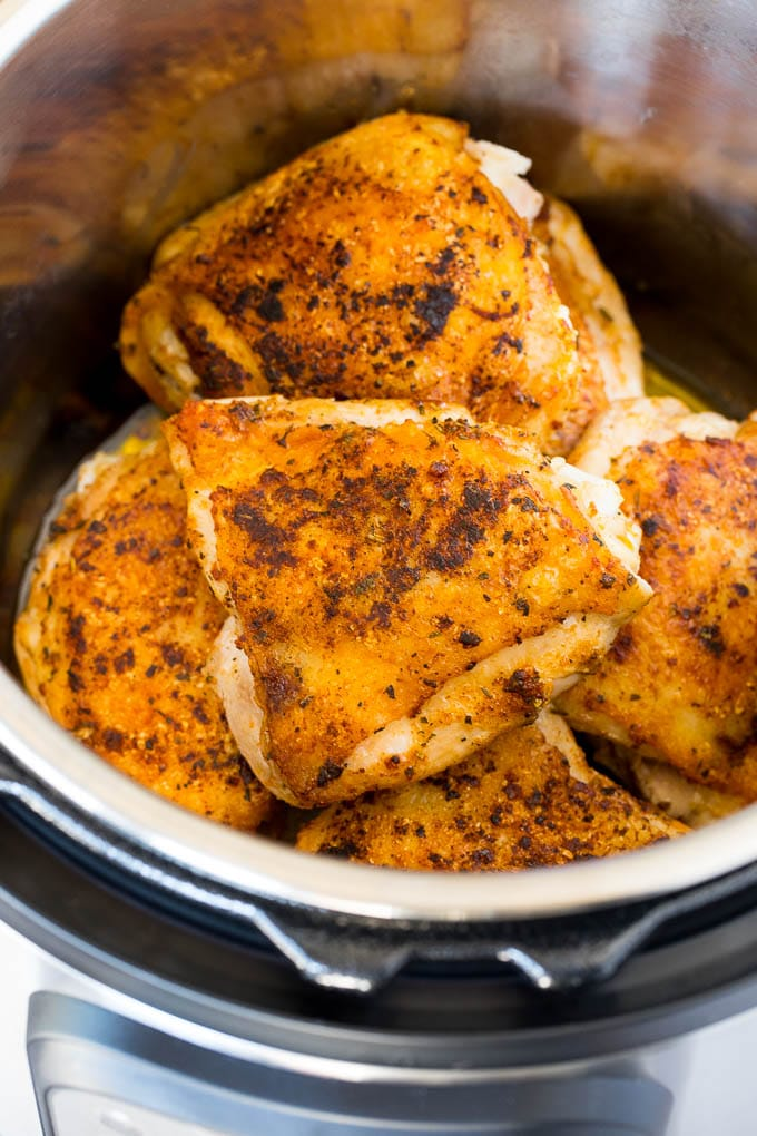 Seared chicken thighs in a pressure cooker.