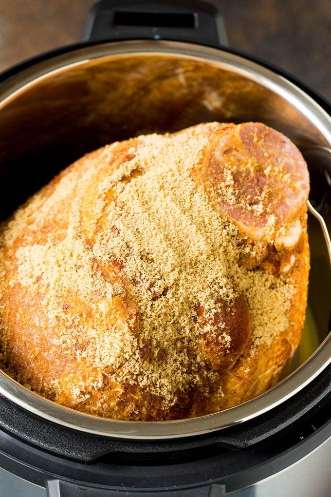 A ham covered in brown sugar in a pressure cooker.
