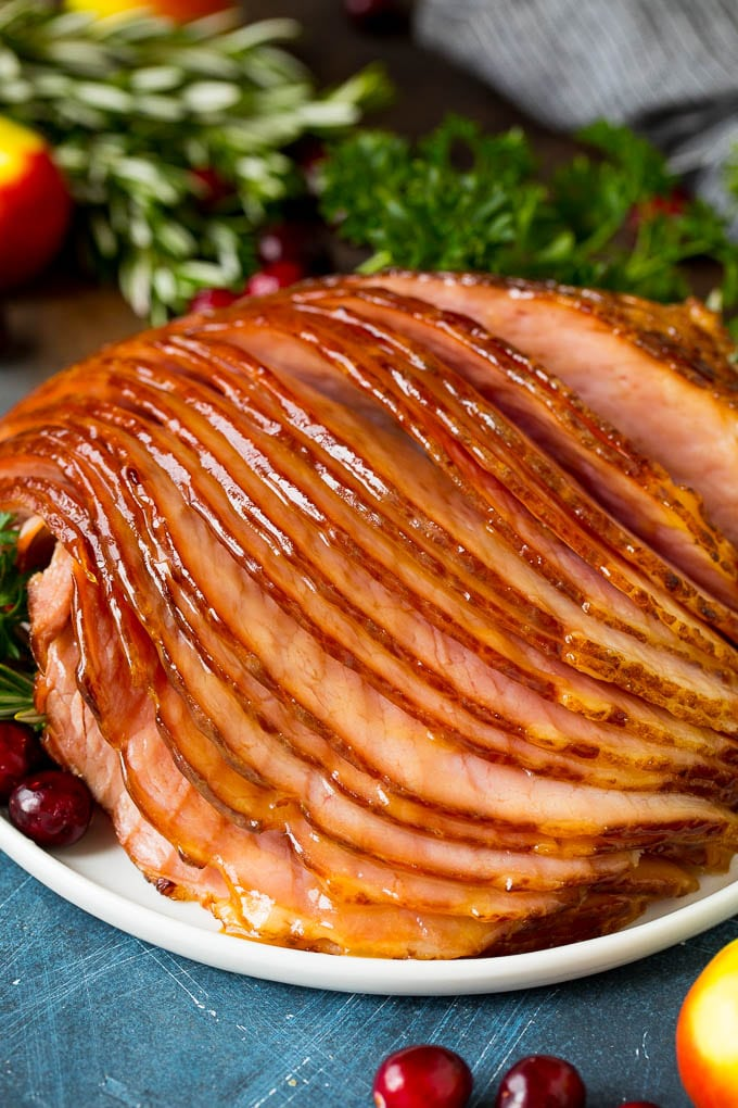 Sliced ham on a plate garnished with cranberries.