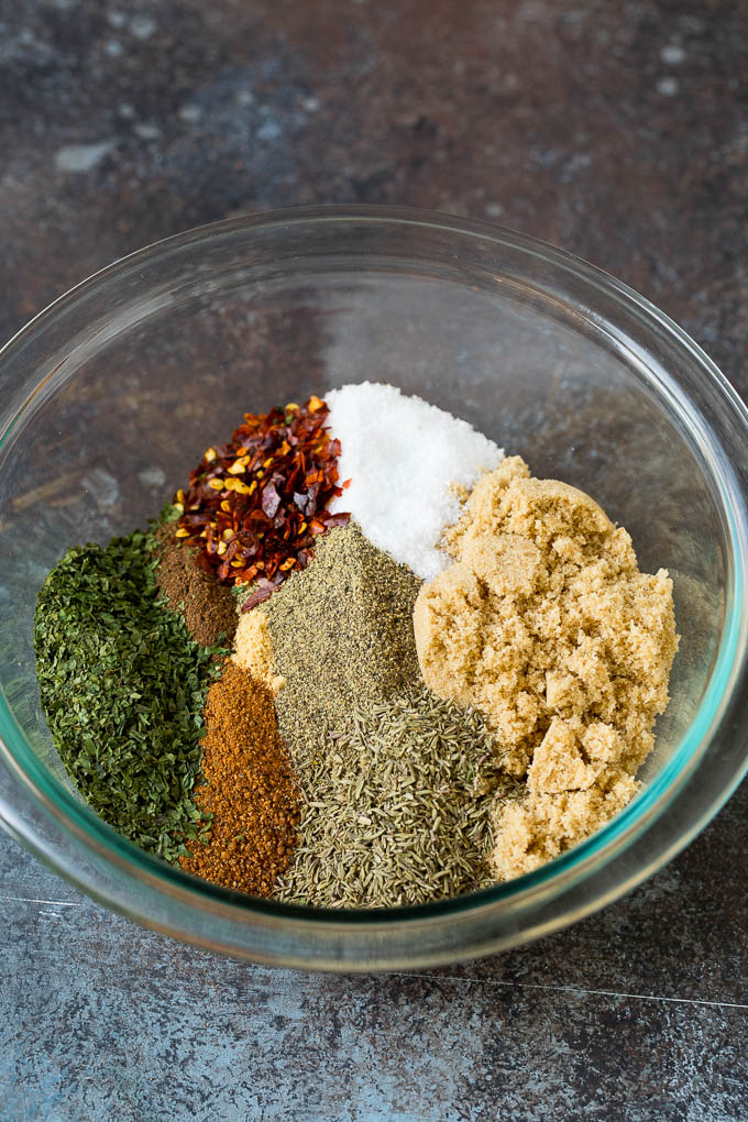 A mixing bowl filled with dried herbs, brown sugar and spices.