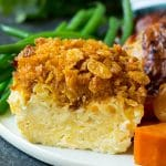 A slice of noodle kugel on a plate with chicken, sweet potatoes and green beans.
