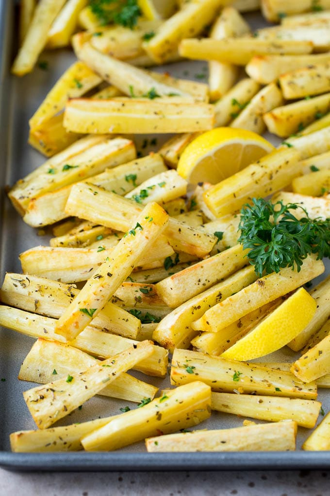 A sheet pan of roasted parsnips garnished with fresh parsley.