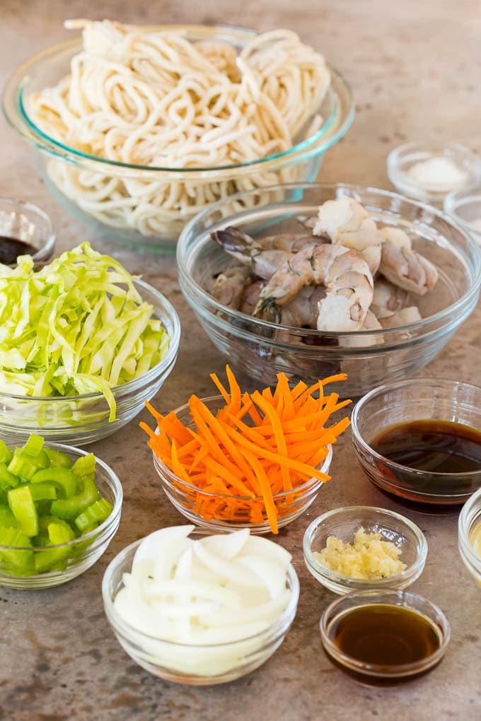 Bowls of ingredients including shrimp, noodles and vegetables.