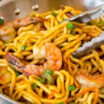 A pan of shrimp lo mein with tongs serving up a portion.
