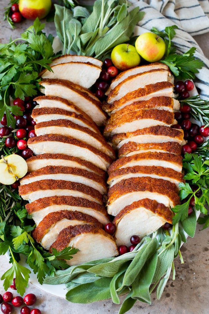 Sliced smoked turkey breast on a serving plate with herbs.