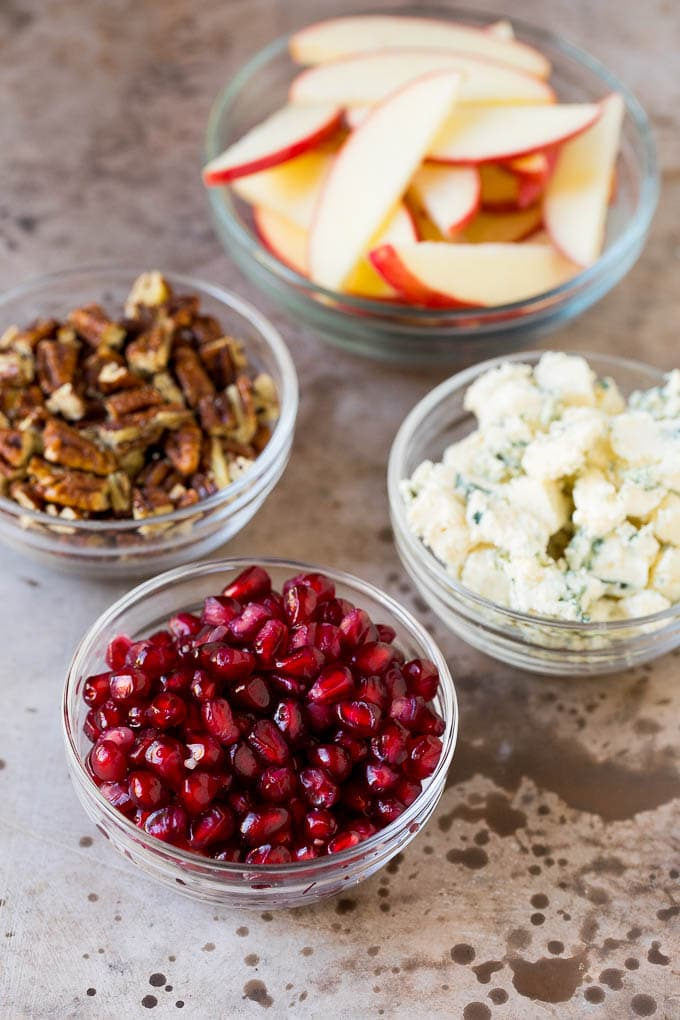 Bowls of cheese, pomegranate arils, apples and pecans.